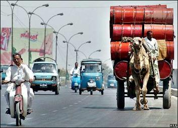 A camel driven cart joins traffic on a busy Karachi road. Image courtesy: BBC